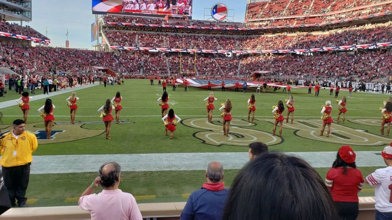 Een cheerleader knielt tijdens de Star-Spangled Banner, vlak voor een footballwedstrijd in de NFL Beeld rv