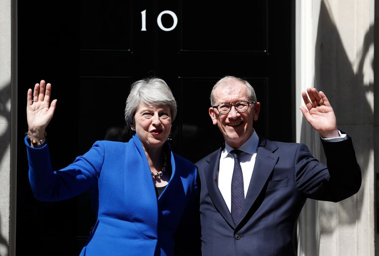 Theresa May en haar man Philip zwaaien nadat ze voor de laatste keer de deur van 10 Downing Street achter zich hebben gesloten. Beeld AP
