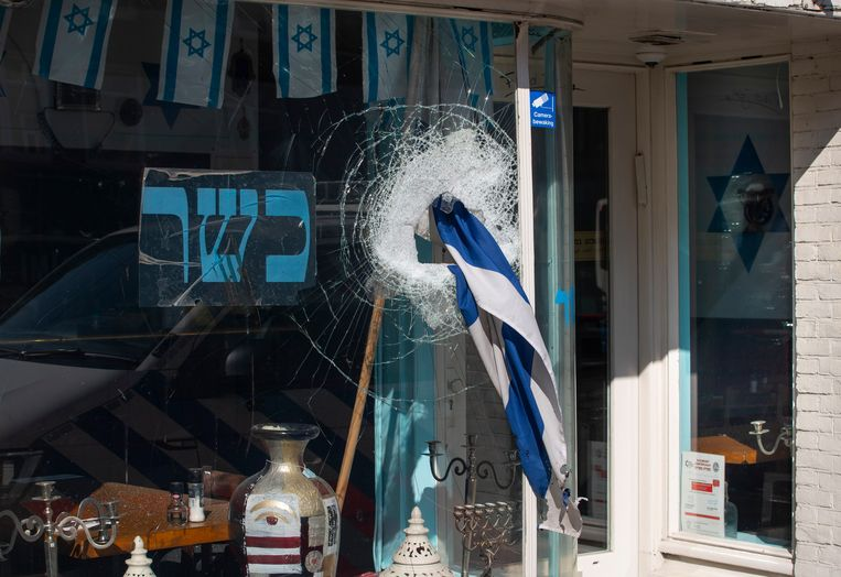 Een Israëlische vlag steekt uit het raam van het koosjere restaurant HaCarmel aan de Amstelveenseweg, nadat een man het raam heeft ingeslagen in mei 2020. Beeld AP