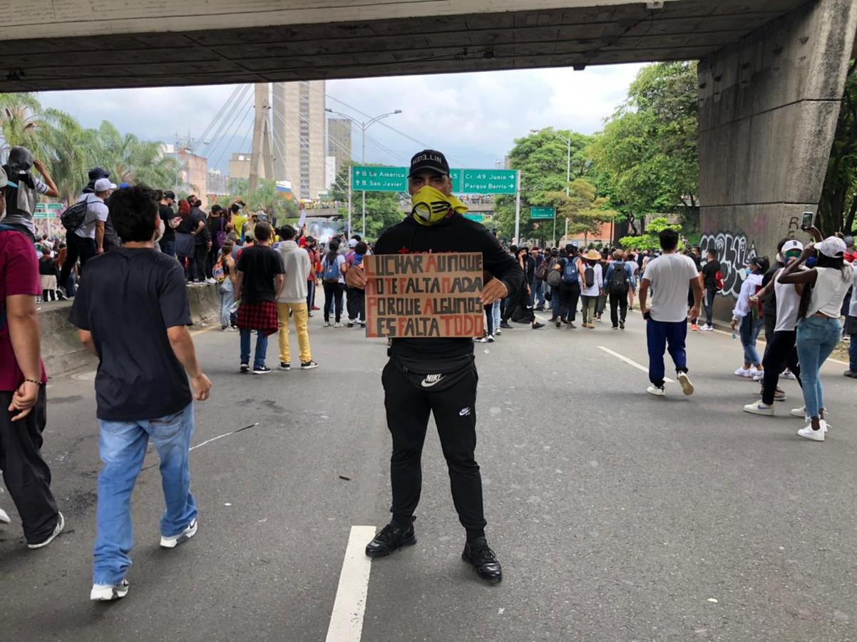 Yino Diaz tijdens het protest in Medellín. Op het bord: 'Ook al kom je zelf niks tekort, vecht voor degenen die alles tekort komen.'