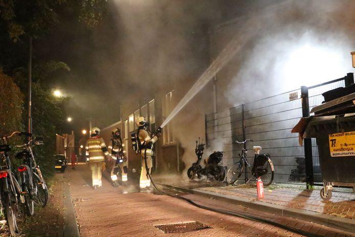 De brandweer houdt het pand nat waar de brandende scooter stond geparkeerd.