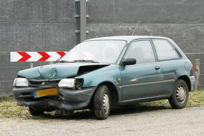 De zwaar beschadigde auto, waarvan de voorkant om de boom krulde.