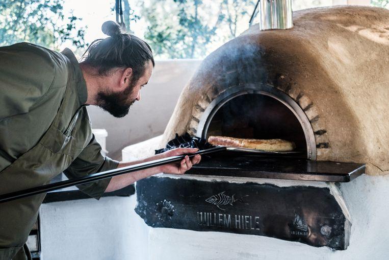 Gastheer Willem Hiele haalt zijn allereerste brood uit zijn nieuwe oven. Beeld Bob Van Mol