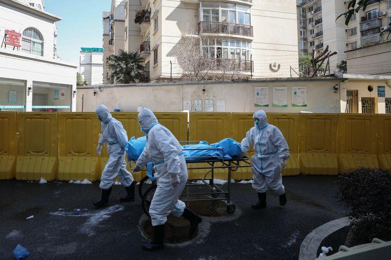 Het lichaam van een covid-19-slachtoffer wordt afgevoerd bij een ziekenhuis in de stad, februari 2020. Beeld EPA
