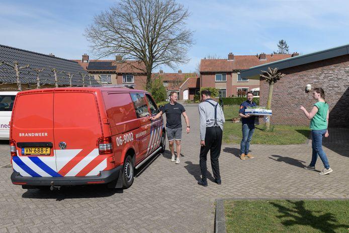 Bas Voortman (links) en Wouter Emsbroek van de vrijwillige brandweer Eibergen bieden paasemmertjes met bloembollen en chocolade aan zorgpersoneel Estinea aan om hen zo hart onder de riem te steken in coronatijd.