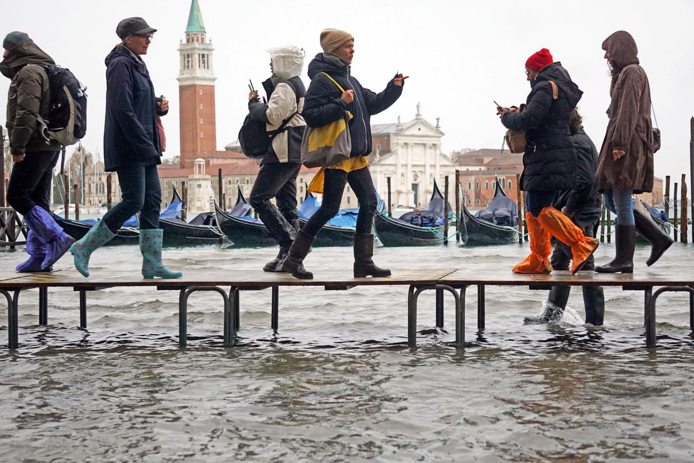 Toeristen lopen over loopplanken door de stad.