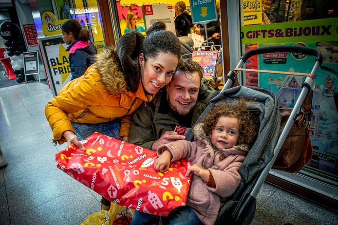 Nicky,  Tommy en dochter Fé kopen Sinterklaas-cadeau's onder het Pieter Vreedeplein. ,,Over een jaar kan dat niet meer met haar erbij, nu heeft ze nog helemaal niets door.'