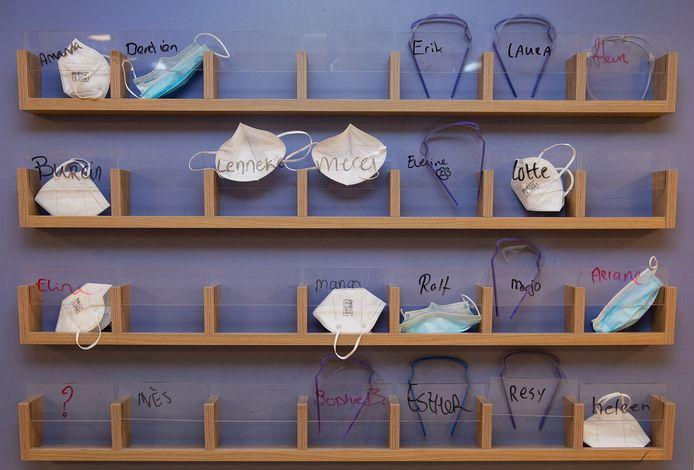 De oude foldervakjes op de covidafdeling dienen nu als 'postvak' voor de verplegers. Allemaal een eigen mondkapje en bril.