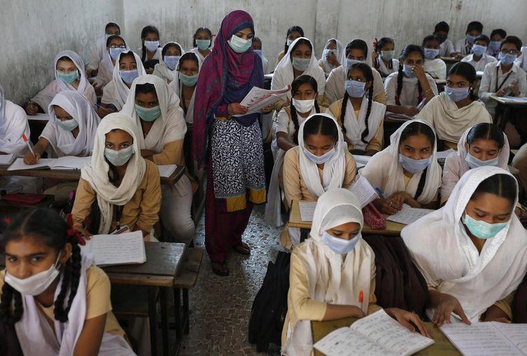 Studenten en de lerares dragen mondmaskers ter bescherming tegen het virus in Ahmedabad. Beeld REUTERS