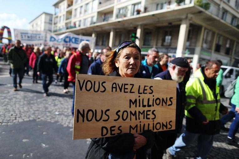 Een vrouw demonstreert in Le Havre. Ze houdt een bord omhoog met de tekst: 'Jullie hebben miljoenen, wij zijn miljoenen' Beeld AFP