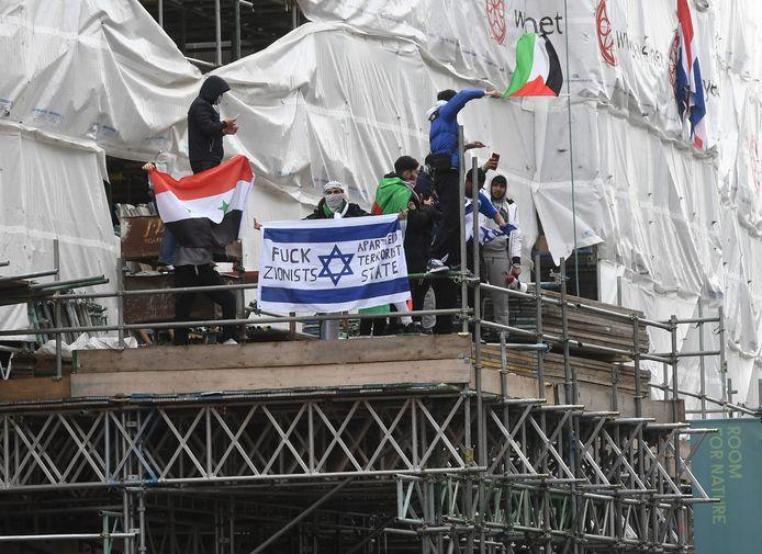 Enkele pro-Palestijnse demonstranten beklimmen een stelling bij de Israëlische ambassade in Londen.