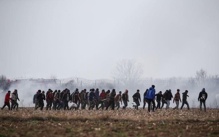 Migranten worden bekogeld met traangas aan de Turks-Griekse grens.  Beeld EPA