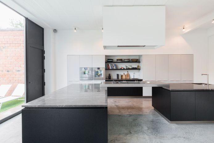 De keuken heeft een werkblad in twee niveaus – handig voor partners die 30 centimeter verschillen in lengte – en twee materialen: natuursteen Grigio Persia en inox.