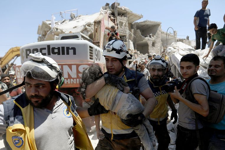 Members of the White helmets carry a wounded child to an ambulance in Maaret al-Numan, Syria. Beeld Hollandse Hoogte / AFP