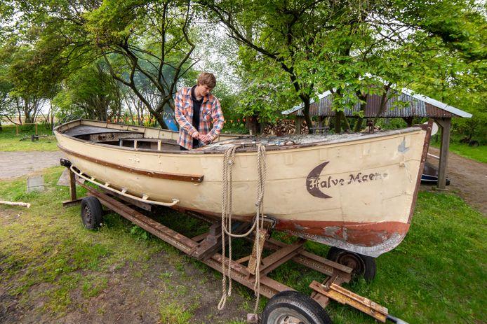 Luuk Montizaan is begonnen met het oplappen van de antieke sloep van de Elburger scouts. De boot raakte ernstig beschadigd door vlammen.