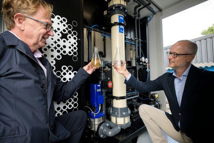 Prof. Erik Roesink (L) en Michiel Staatsen van bedrijf NX Filtration. met ongezuiverd en gezuiverd water uit het Twentekanaal.