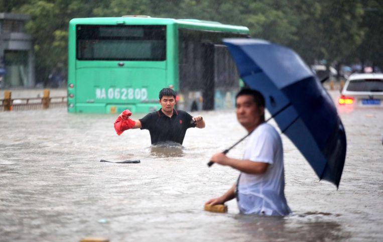 Zo goed en zo kwaad als dat gaat steken inwoners van Zhengzhou de straat over. Beeld EPA