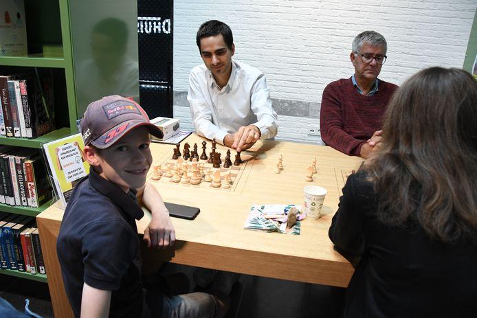 Boris Verboom(12) kijkt even op, maar tegen een crack als Twan Burg kan hij beter de aandacht bij de stelling op het bord houden. Naast de schaakgrootmeester bevindt zich vader Henk Burg