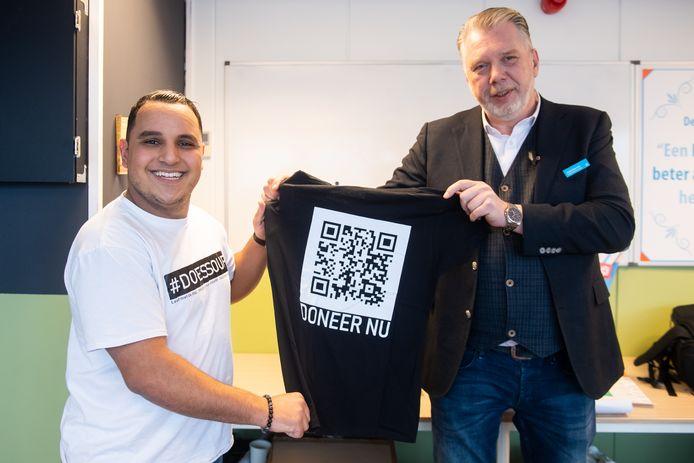 Soufiane Elazizi bij de lancering van zijn fonds. Samen met André Boersma van Albert Heijn toont hij een shirt met de QR-code om te kunnen doneren.