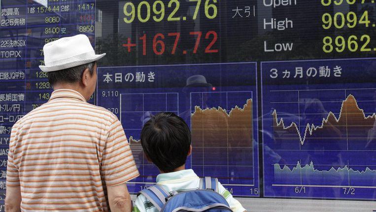 Man en kind bekijken de aandelenkoersen in een etalage in Tokyo. Beeld ap