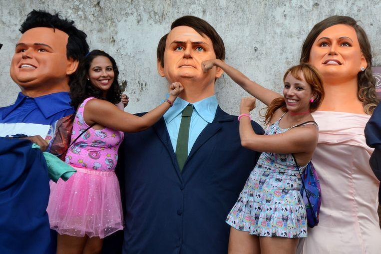 Twee Braziliaanse vrouwen steken de draak met president Jair Bolsonaro tijdens een carnavalsoptocht, maandag, in Olinda. Beeld EPA