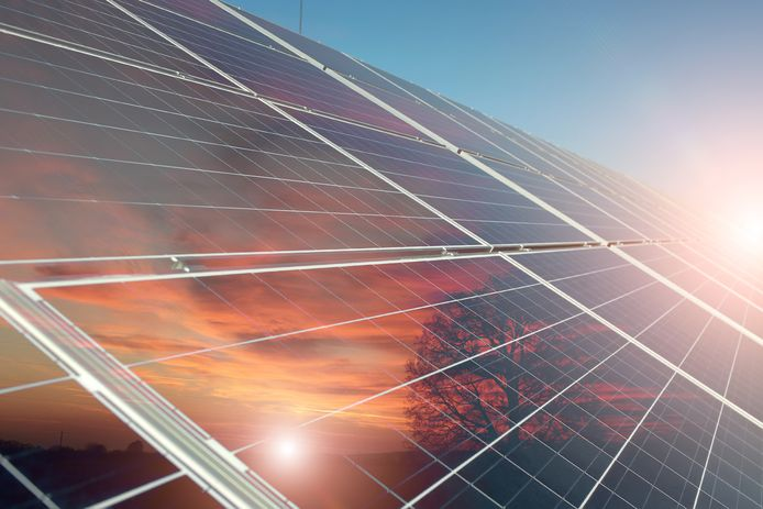 stockadr zonnepanelen zonne-energie Solar battery with reflection of orange sunset with tree on clear blue sky with highlight background, horizontal picture