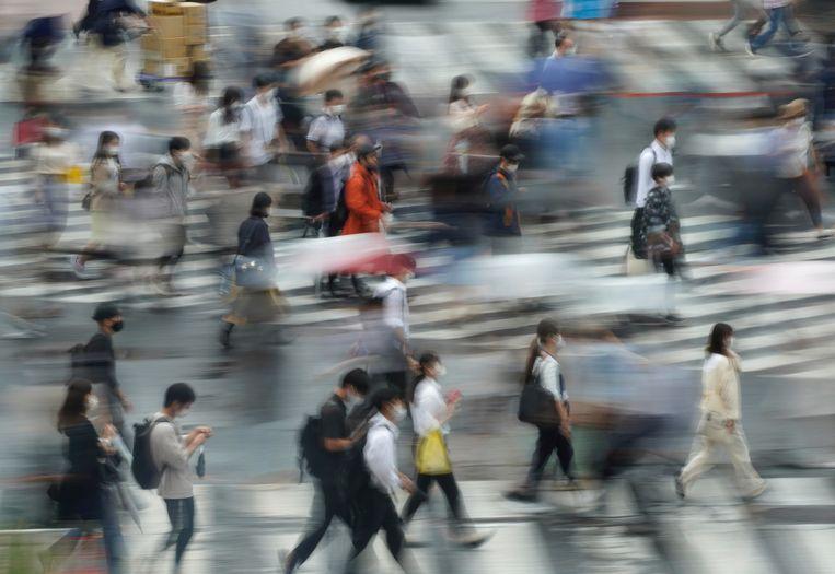 Voetgangers steken over bij het Shibuyakruispunt in Tokio. Zolang niemand op zijn telefoon tuurt, botsen ze niet.  Beeld EPA