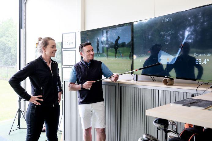 Golfcoach leraar Lee Chapman doet met een van zijn leerlingen een analyse op  het grote schermen.