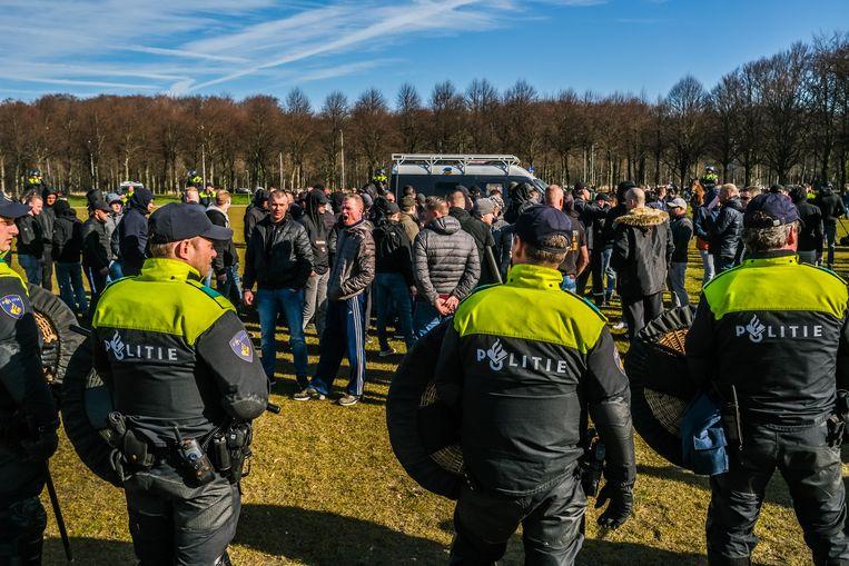 ADO Den Haag-supporters worden door de ME staande gehouden op het Malieveld omdat ze de confrontatie wilden aangaan met Ajax-fans, februari 2019.  Beeld Joris van Gennip
