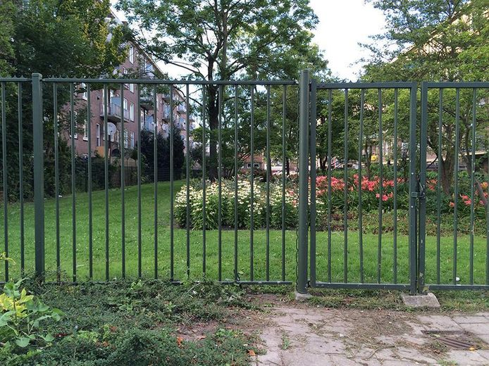 Het hek voor de binnentuin in Amsterdam-West. Liana kroop er door de spijlen heen.