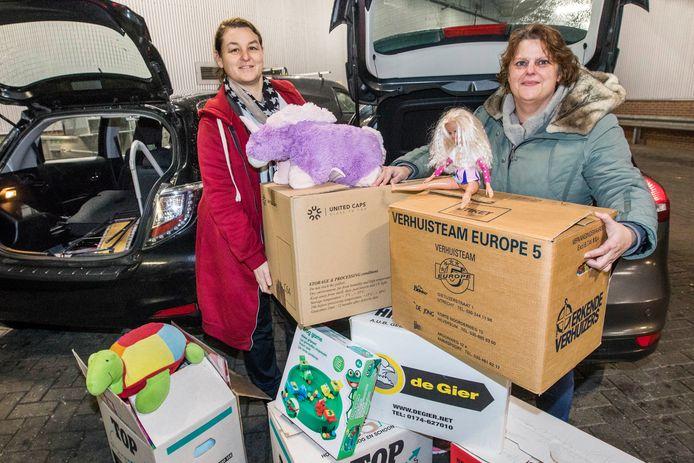 Joyce van Loon, beheerder van Voedselgroep Zoetermeer (rechts) en medewerkster Manya van der Poel staan bij de expeditie van het Woonhart met dozen vol speelgoed om weg te geven met Sinterklaas.