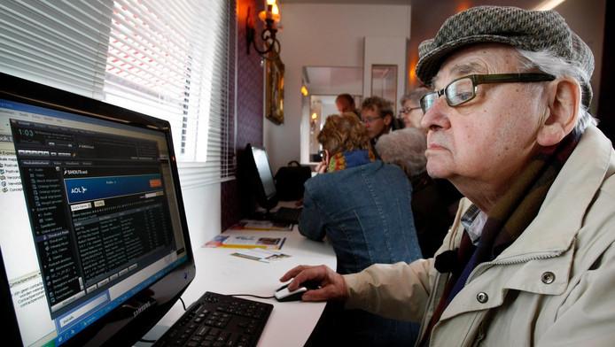 Een oudere achter een computer.