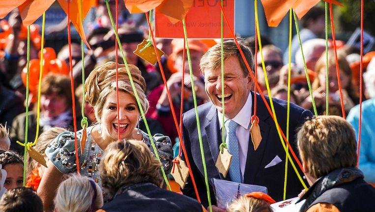 Koning Willem-Alexander en koningin Máxima in gesprek met Oranjefans langs de route in De Rijp. Beeld ANP