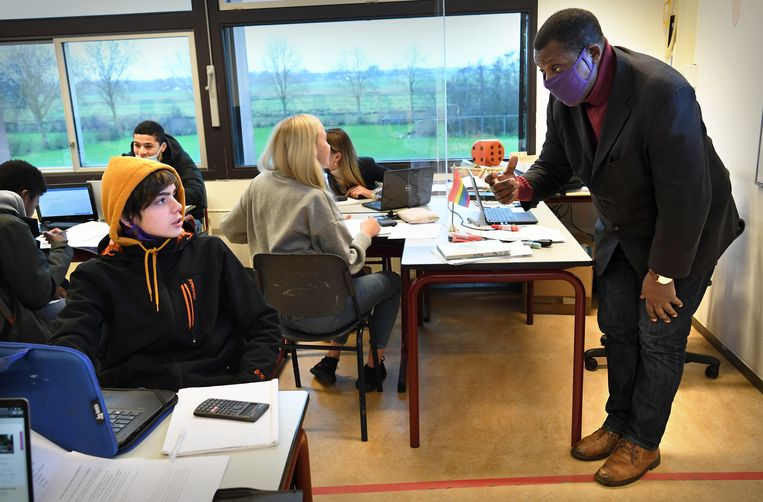 Met jassen en dikke truien aan in het klaslokaal waar de ramen open moeten blijven voor frisse lucht tegen de verspreiding van het coronavirus. Beeld Marcel van den Bergh / de Volkskrant