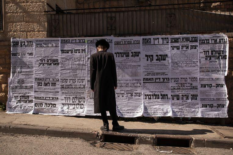 Een man bekijkt de talloze rouwadvertenties aan een muur in Mea Shearim.  Beeld NYT