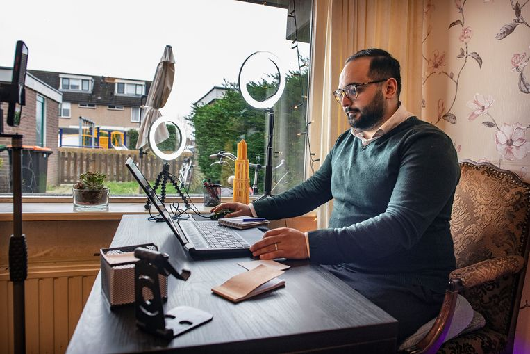 De Syrische Alomari achter zijn bureau, waar hij livestreams opneemt voor Arabischtalige nieuwkomers in Nederland. Beeld Guus Dubbelman / de Volkskrant