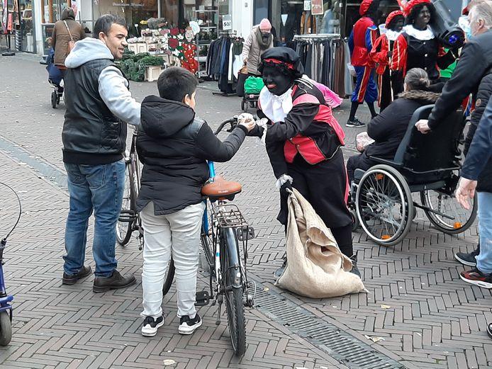 Zwarte Piet deelt snoepgoed uit in het centrum van Tiel