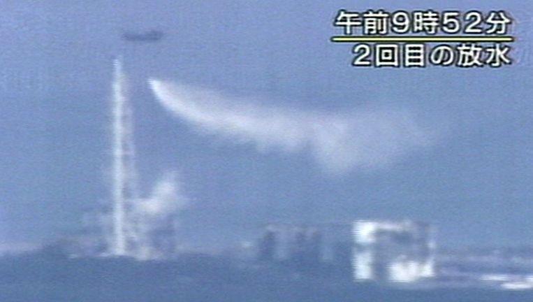 Van grote afstand is te zien hoe een helikopter zeewater op de kerncentrale loost Beeld ap