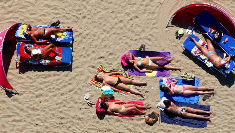 Het strand van Zandvoort ligt helemaal vol met strandbezoekers uit de stad. Nederlanders genieten eindelijk van een zomers weekeinde. Beeld ANP