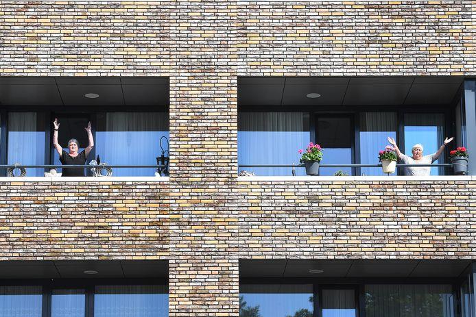 Bewoners van zorgcentrum Symfonie in Boxmeer bewegen mee op hun balkon.