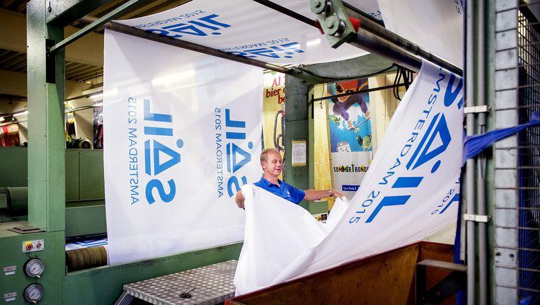 De Dokkumer Vlaggen Centrale print de vlaggen voor de deelnemende schepen aan het maritiem evenement Sail Amsterdam. Beeld anp