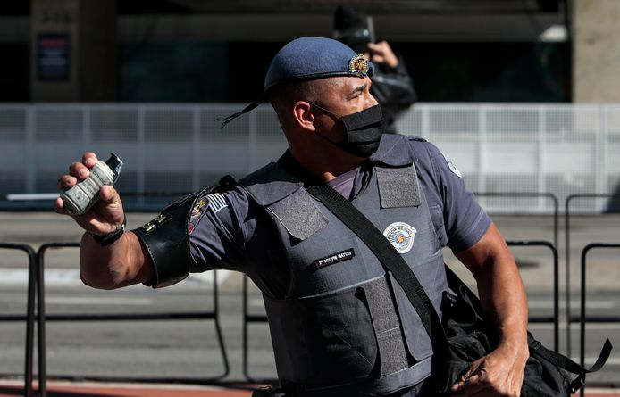 Een agent in São Paulo werpt een traangasgranaat.