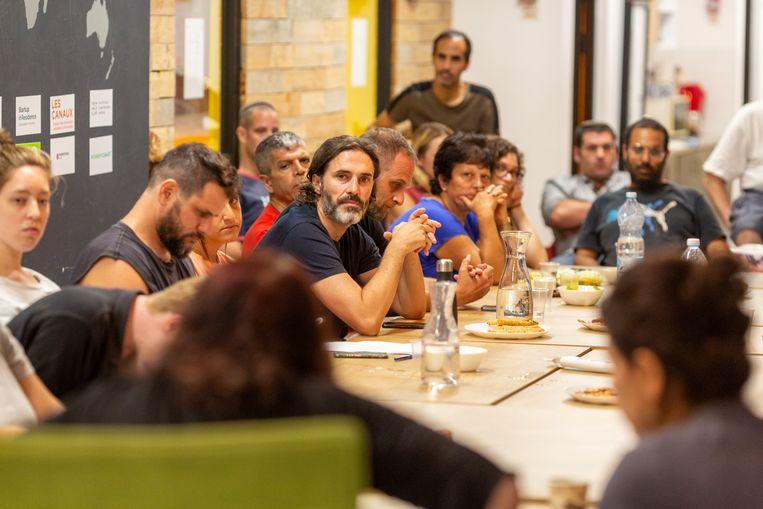 Ivry Baumgarten (midden, met baard) tijdens een bijeenkomst in buurtcentrum 'Het Lokaal' in Tel Aviv. Beeld Geert van Kesteren