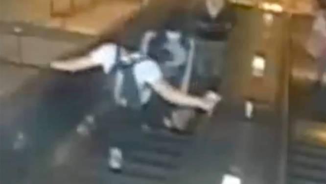 Un homme pousse une femme dans l'escalator d'une station de métro