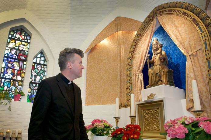 Pastoor Henri ten Have bij het beeld van Maria van Renkum dat helende krachten zou bezitten.