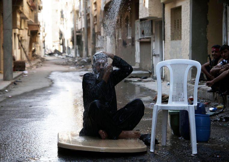 Een strijder van het Vrije Syrische Leger neemt een douche op straat in Deir al-Zor. Beeld reuters