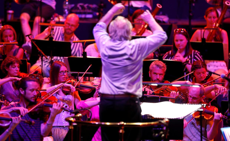 Steeds vaker heeft de dirigent vrouwelijke musici voor zich. Hierboven dirigent Nicholas Dodd en het Albert's Orchestra tijdens een repetitie in de Royal Albert Hall in Londen, 19 juli 2021.   Beeld Reuters