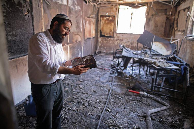 Een rabbi neemt de schade op in een religieuze school in Lod, die eerder op de dag al afbrandde. Beeld AFP