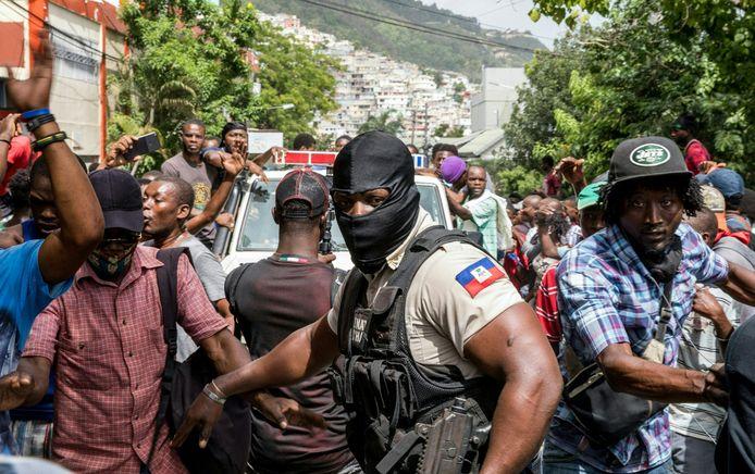 Politie en mensen op straat in Haïti bij het politiebureau waar de verdachten van de moord op de president worden vastgehouden.