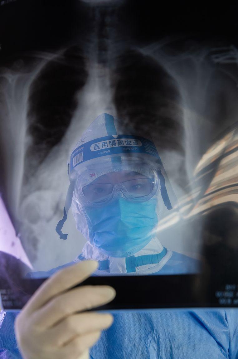 Een dokter bekijkt een röntgenfoto in een ziekenhuis in Wuhan.  Beeld Barcroft Media via Getty Images